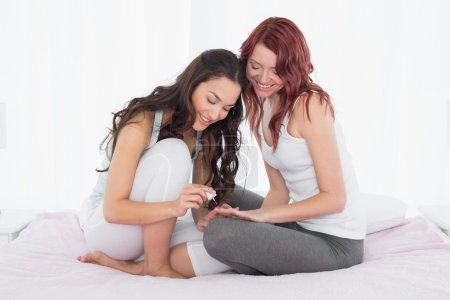 Photo pour Toute la longueur des clous de l'ami de peinture d'une jolie jeune femme sur le lit à la maison - image libre de droit
