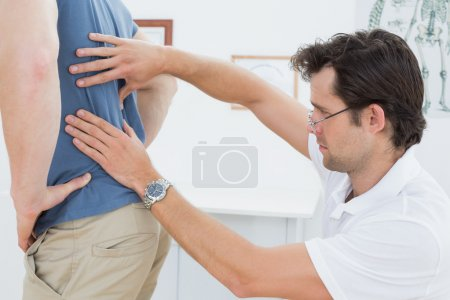 Mid section of a physiotherapist examining mans back