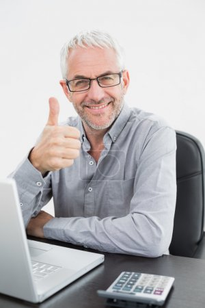 Smiling businessman with laptop gesturing thumbs up