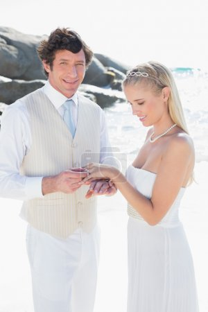 Man placing ring on pretty brides finger
