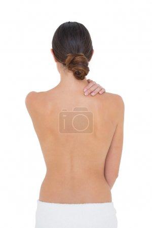 Foto de Vista posterior de una mujer joven apta en topless con dolor del hombro sobre fondo blanco - Imagen libre de derechos