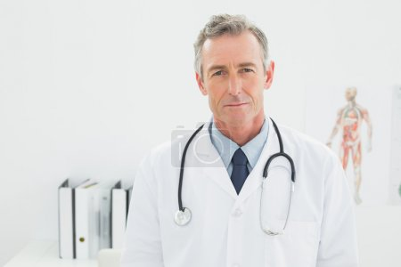 Smiling confident male doctor in medical office