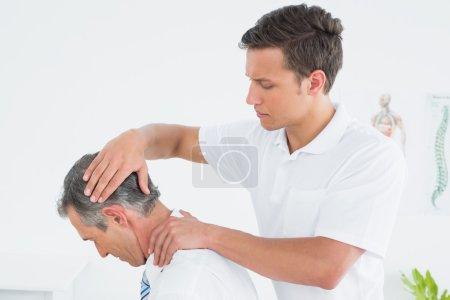 Foto de Quiropráctico masculino masaje cuello pacientes sobre fondo blanco - Imagen libre de derechos
