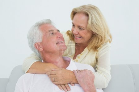 Photo for Portrait of a happy senior woman embracing man from behind at home - Royalty Free Image