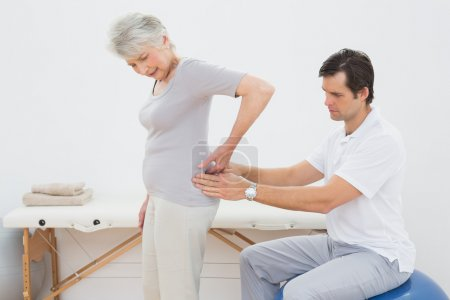 Male physiotherapist examining senior woman's back
