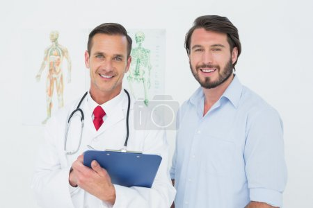 Portrait of a male doctor and patient with reports