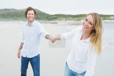 Photo for Portrait of a smiling casual young couple holding hands at the beach - Royalty Free Image