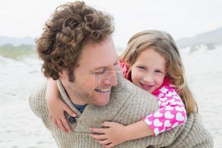Man piggybacking his daughter at beach