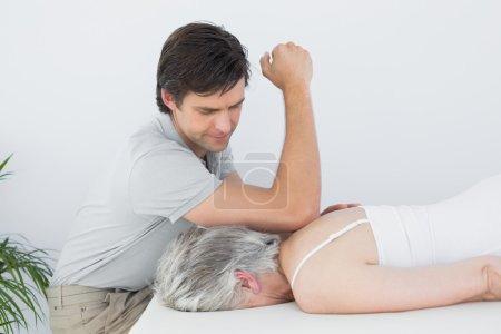 Male physiotherapist massaging a senior woman's back
