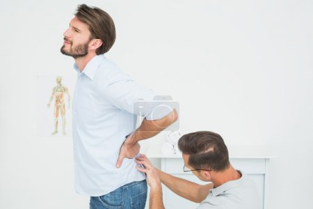 Photo for Side view of a male physiotherapist examining man's back in the medical office - Royalty Free Image