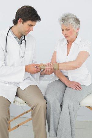 Male physiotherapist examining a senior woman's wrist