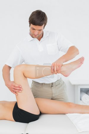 Male physiotherapist examining a young woman's leg