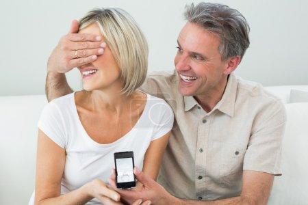 homme yeux de couverture de la femme pour lui offrir une bague de fiançailles