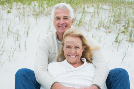 Photo for Romantic senior man and woman relaxing on sand at the beach - Royalty Free Image