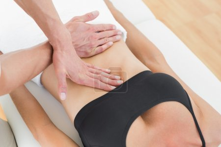 Mid section of a physiotherapist massaging woman's body