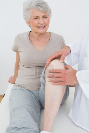 Displeased senior woman getting her knee examined