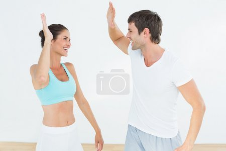 Cheerful fit young couple giving high five