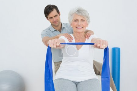 Photo for Male therapist assisting senior woman with exercises in the medical office - Royalty Free Image