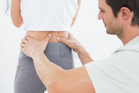 Mid section of a physiotherapist examining woman's back