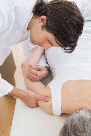 Physiotherapist massaging a senior woman's arm