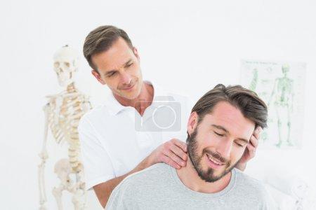Photo pour Chiropraticien masculin faisant ajustement du cou dans le bureau médical - image libre de droit