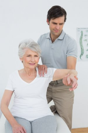Male physiotherapist stretching a senior woman's arm