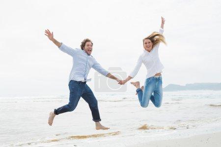 Photo pour Toute la longueur d'un jeune couple joyeux tenant la main et sautant à la plage - image libre de droit