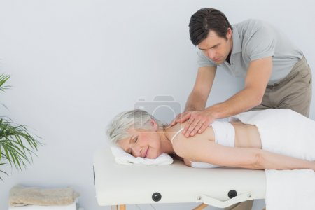 Photo for Male physiotherapist massaging a senior woman's back in the medical office - Royalty Free Image