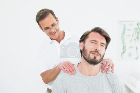 Male therapist massaging a content man's shoulders