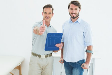 Therapist gesturing thumbs up with disabled patient
