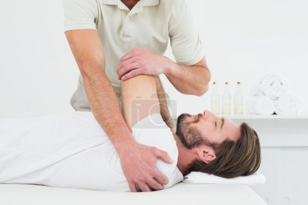 Male physiotherapist stretching a young man's hand