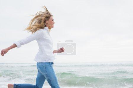 Photo pour Vue latérale d'une jeune femme souriante et décontractée courant sur la plage - image libre de droit