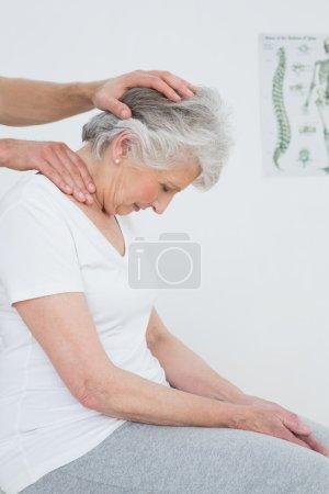 Foto de Vista lateral de una mujer mayor que el ajuste del cuello en el consultorio médico - Imagen libre de derechos