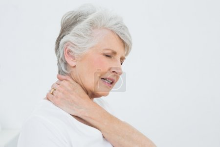 Side view of a senior woman suffering from neck pain