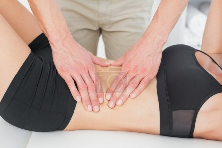 Photo for Close-up mid section of a physiotherapist massaging woman's body in the medical office - Royalty Free Image