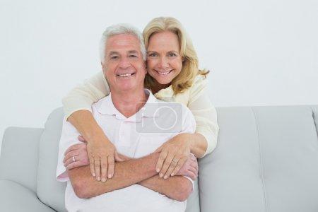 Feliz mujer mayor abrazando al hombre por detrás