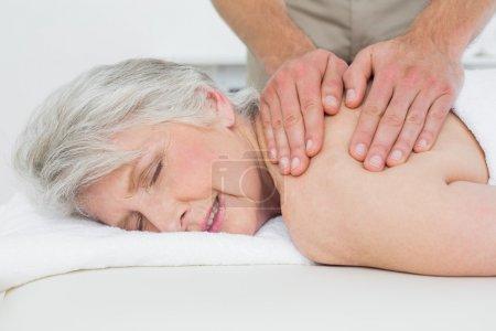 Physiotherapist massaging a senior woman's back