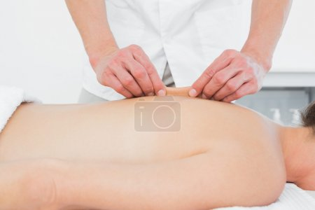 Mid section of a physiotherapist massaging woman's back