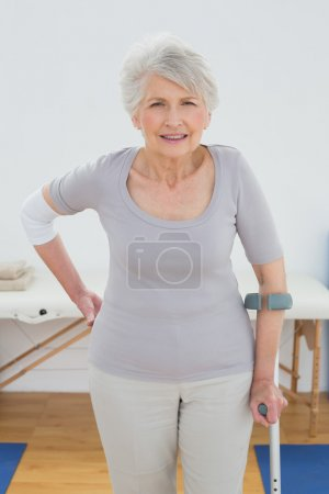 Photo for Portrait of a senior woman with crutch standing in the hospital gym - Royalty Free Image