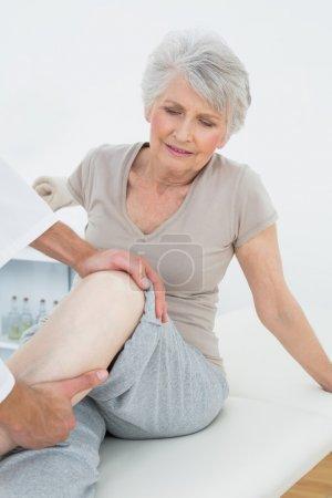 Displeased senior woman getting her leg examined