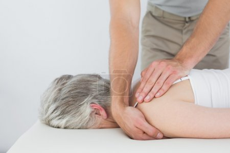 Photo for Male physiotherapist massaging a senior woman's shoulder in the medical office - Royalty Free Image