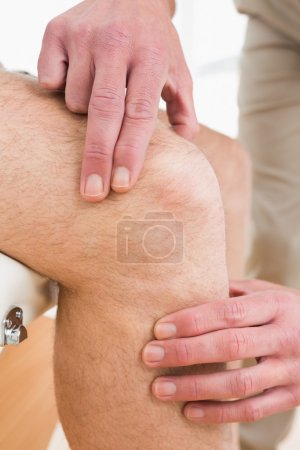 Close-up mid section of a man getting his knee examined