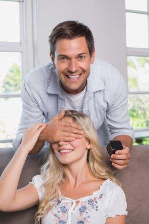 souriant homme surprenant avec une bague de mariage à la maison