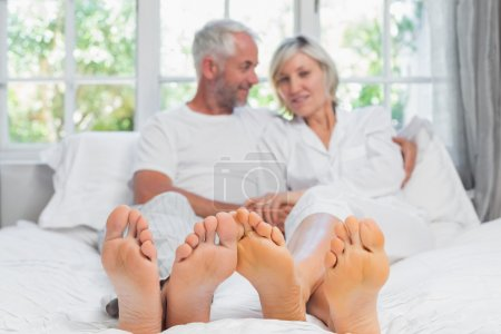Portrait of a mature couple sitting in bed