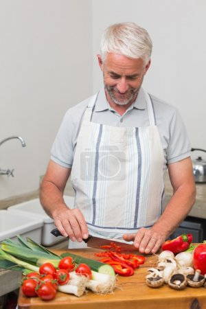 Photo for Mature man chopping vegetables in the kitchen at home - Royalty Free Image