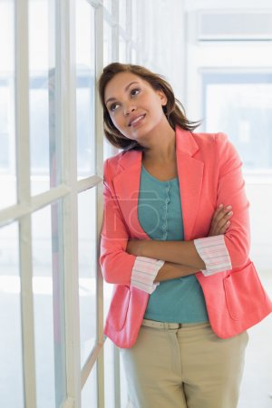 Photo for Thoughtful young businesswoman looking away at a bright office - Royalty Free Image
