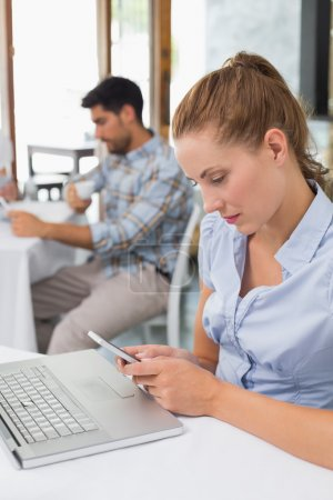 Woman using laptop and mobile phone in coffee shop