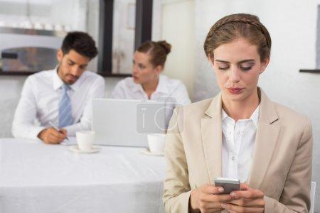 Photo pour SMS que femme d'affaires avec des collègues en réunion derrière au bureau - image libre de droit