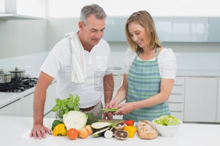 Photo for Portrait of a happy couple preparing food together in the kitchen at home - Royalty Free Image