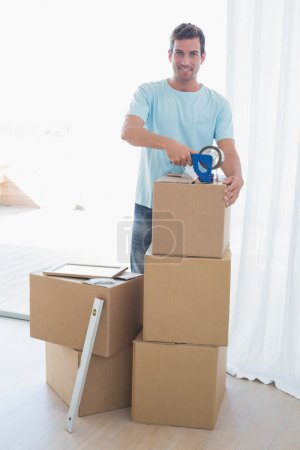 Photo for Portrait of a smiling young man with cardboard boxes in new house - Royalty Free Image